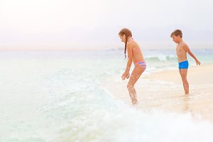 Brother and sister playing together on sea shore