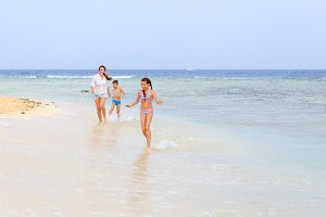 Young woman with children enjoying beach vacation