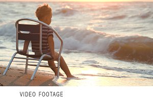 Boy sitting alone the chair by sea