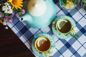 Teapot, green tea with lemon in the cups, chamomile and mint decorations
