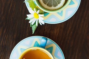 Cups with herbal tea, lemon, mint leaves and different herbs