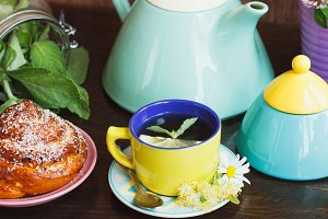 Green tea with lemon, mint and baked goods on the plate