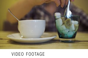 Woman putting sugar into tea cup