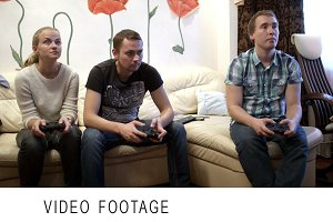 Two men and girl playing video game