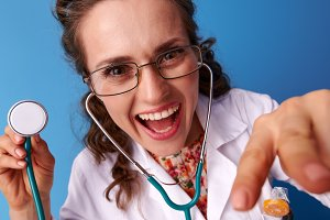 pediatrist woman with stethoscope distracting child playing