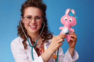 smiling pediatrist woman listening toy with stethoscope on blue