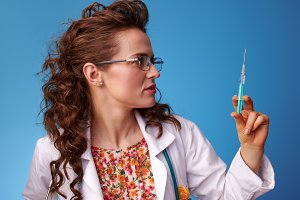 paediatrician woman looking at syringe on blue