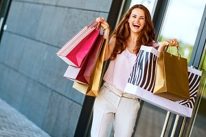 Happy young woman with shopping bags rejoicing near shop door