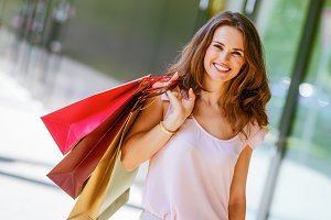 happy young woman with shopping bags on the mall all