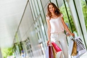 Happy young woman with shopping bags walking on the mall alley