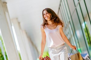 Young woman with shopping bags walking on the mall alley