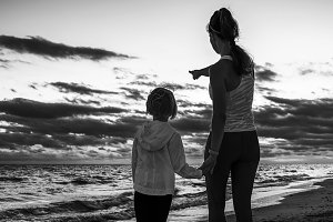 mother and child on seashore on sunset pointing at something