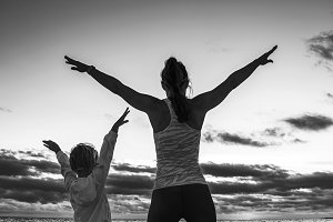 active mother and child on seashore on sunset rejoicing