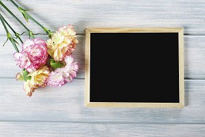 Close up of pink and yellow flowers next to blackboard on wooden table. Copyspace Mockup.