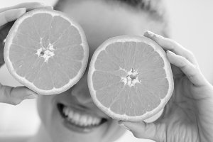 Happy young woman holding two slices of orange in front of eyes