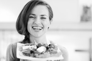 Smiling young woman showing fresh salad
