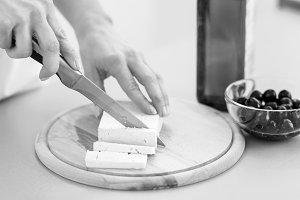 Closeup on woman cutting fresh cheese