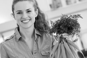 Happy young housewife holding bunch of carrots in kitchen