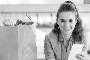 Smiling young housewife examines purchases and check after shopping in kitchen