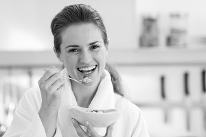 Smiling young woman in bathrobe having healthy breakfast