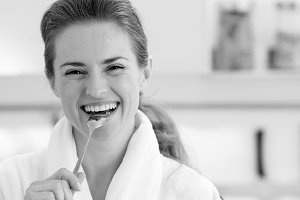 Smiling young woman in bathrobe eating healthy breakfast