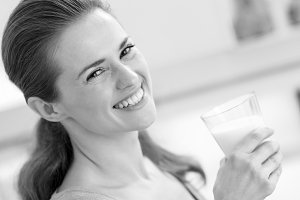 smiling young woman with glass of milk in kitchen