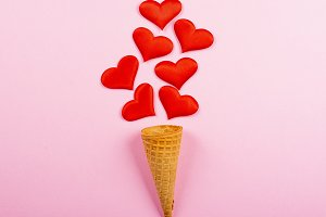 Red hearts sticking out of ice cream cookie on pink background. Conceptual about love. Minimal