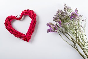 Close up of lilac flowers next to red heart on white background. Isolated. Copyspace