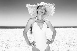 Portrait of pensive young woman in beachwear on beach