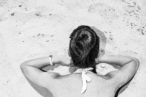 Seen from behind modern woman in swimwear laying on seacoast