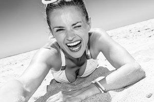 smiling modern woman in swimsuit on beach taking selfie