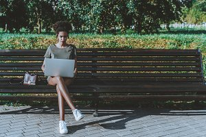 Girl with laptop on park bench