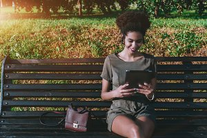 Black girl with tablet pc on bench