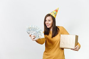 Caucasian fun young happy woman in yellow clothes, birthday party hat holding golden gift box with present and wad of cash money, celebrating holiday on white background isolated for advertisement.