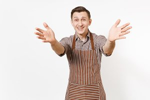 Young happy smiling man chef or waiter in striped brown apron, shirt stretching hands to camera isolated on white background. Male good housekeeper or houseworker. Domestic worker for advertisement.