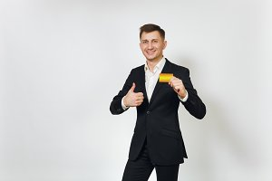Young successful handsome rich business man in black suit holding golden credit card isolated on white background for advertising. Concept of money, achievement, career and wealth in 25-30 years.