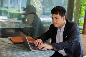 Young Asian businessman working on his laptop in outdoor scene