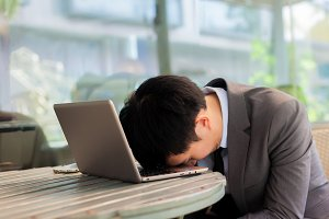 Businessman tiring and sleeping on his laptop in outdoor scene - overworked concept