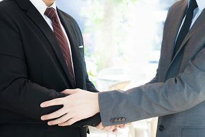 Two businessmen giving warm welcome, trust, teamwork, agreement to each other concept