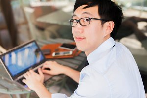 Young Asian businessman working on laptop in outdoor workplace