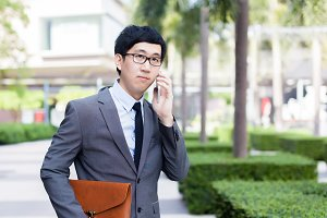 Young Asian businessman in elegant suit talking on the phone with serious face