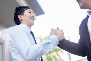 Two Asian businessmen giving warm welcome, trust, teamwork, agreement to each other concept