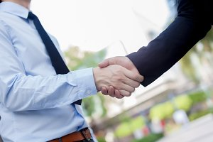 Handshake between new employee with messy sleeves and boss - bad first impression concept