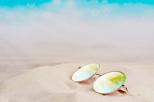 Sunglasses with reflection of palm trees and sky laying on a sandy tropical beach