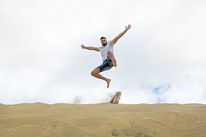 Tourist jumping on the sand dunes