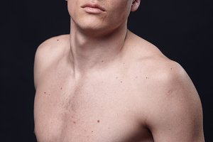 one young handsome man, model shirtless, simple studio upper body shot, black background.