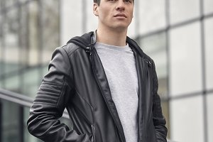 one young handsome man posing outdoors, wearing jacket, casual clothes, upper body shot, modern architecture building behind.