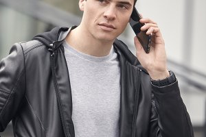 one young handsome man posing outdoors, wearing jacket, talking over smartphone telephone, casual clothes, modern architecture building behind.