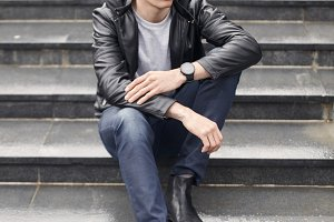 handsome man sitting on steps, wearing casual clothes. overcast autumn day.