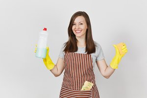 Young housewife in yellow gloves, striped apron, cleaning rag in pocket isolated on white background. Woman holding bottle with cleaner liquid for washing dishes, sponge. Copy space for advertisement.